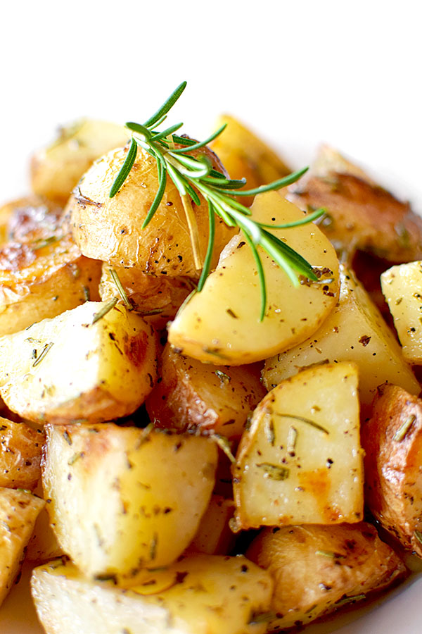 a pile of roasted potatoes with rosemary on a white plate