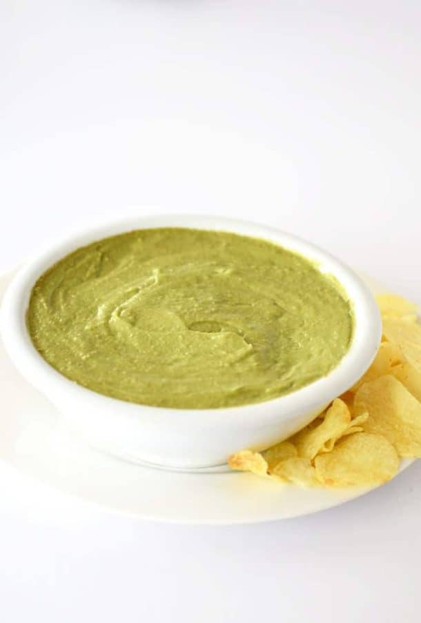 Avocado dip in a white bowl with potato chips on the side