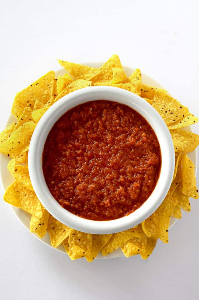 Birds eye view of restaurant style salsa in a bowl surrounded by corn chips