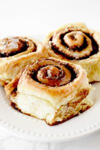 three dairy free cinnamon rolls on a white plate