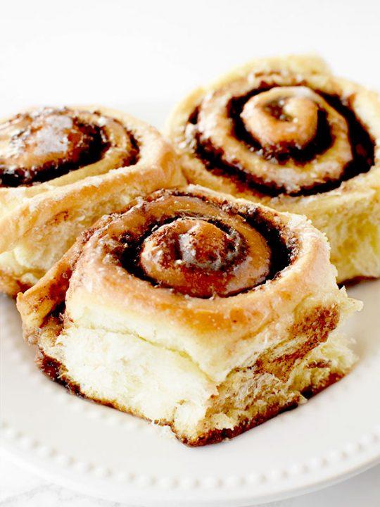 three dairy free cinnamon rolls on a white plate