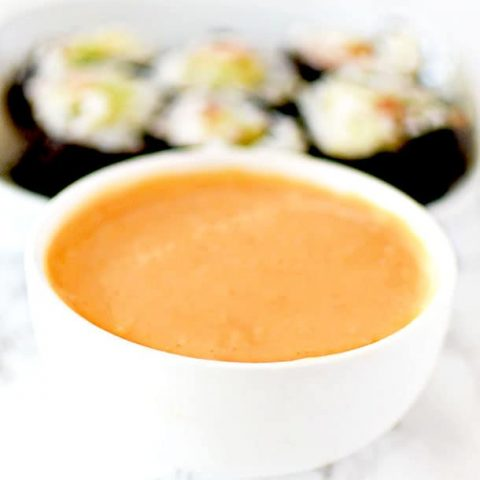Spicy mayo in a dipping bowl with sushi in the background