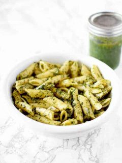 a bowl of dairy free (vegan) pasta with pesto and a jar of pesto sauce in the background
