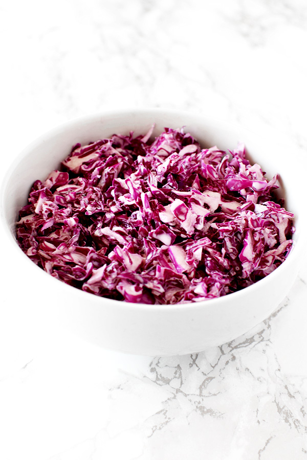 Israeli red cabbage salad in a white bowl on a white marble counter
