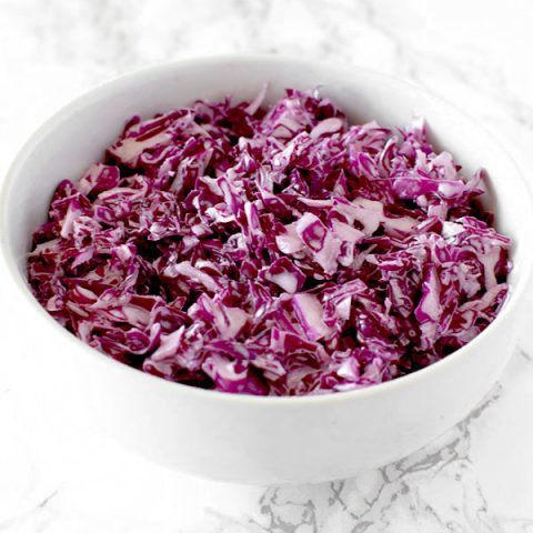 bowl of israeli red cabbage salad on a white counter