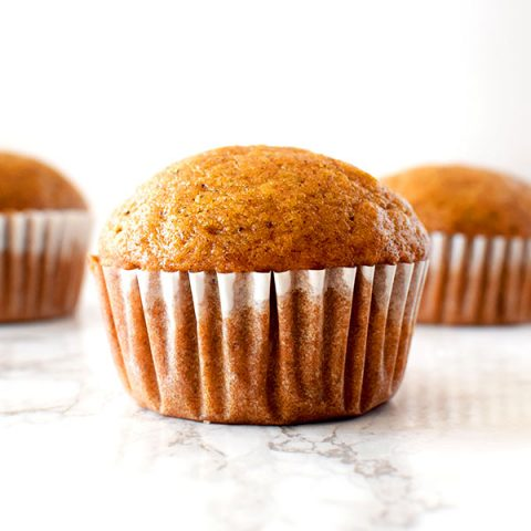 Three butternut squash muffins sitting on a white marble counter