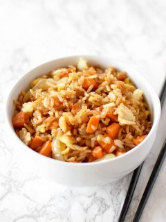 fried rice in a white bowl on a white marble counter