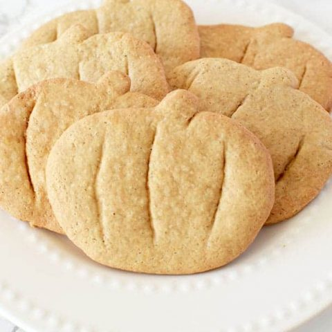 pumpkin spice cookies cut into pumpkin shapes on a white plate