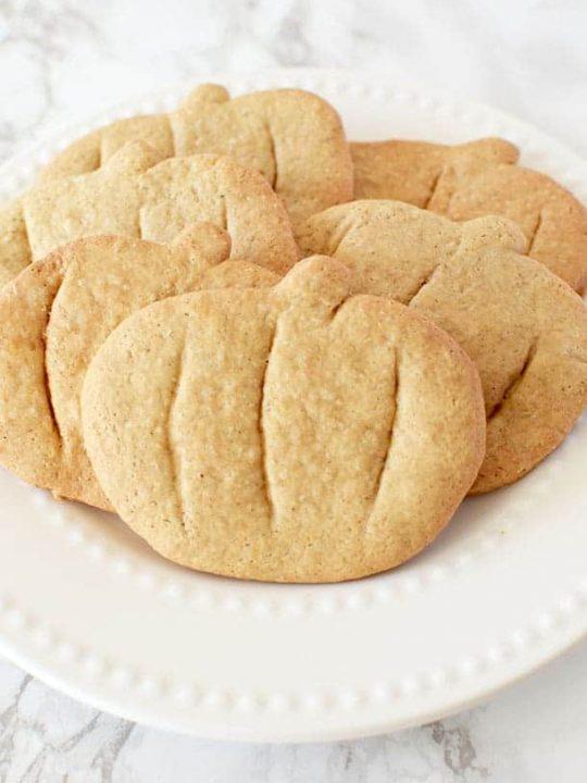 pumpkin spice cookies cut into pumpkin shapes on a white plate