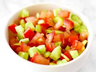 Israeli salad in a white bowl on a white marble counter