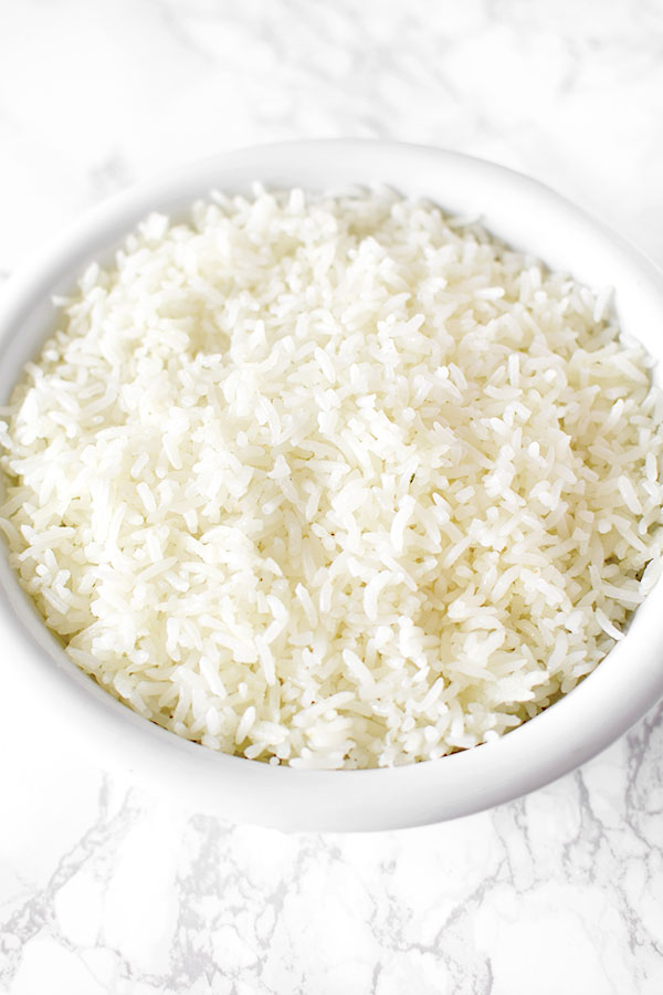 white rice in a white bowl on a marble counter