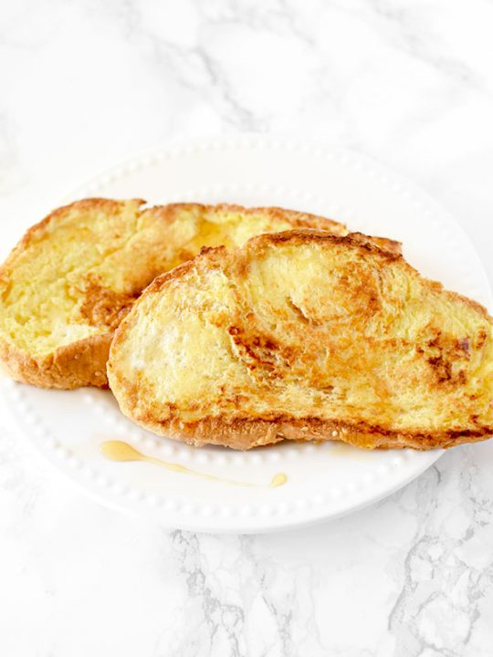 French toast on a white plate on a white marble counter