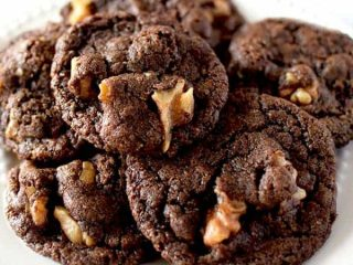 Chocolate cookies with walnuts on a white plate