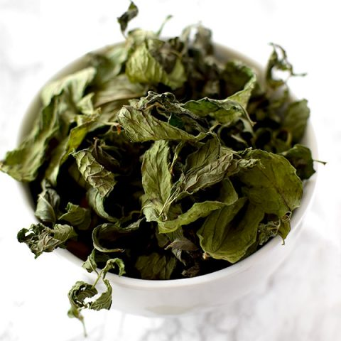 dried mint leaves in a white bowl on a counter