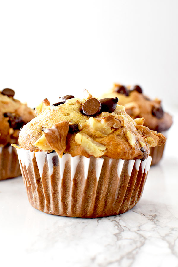 three chocolate chip banana nut muffins on a white marble counter
