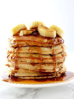 Stack of banana pancakes topped with bananas and dripping in maple syrup