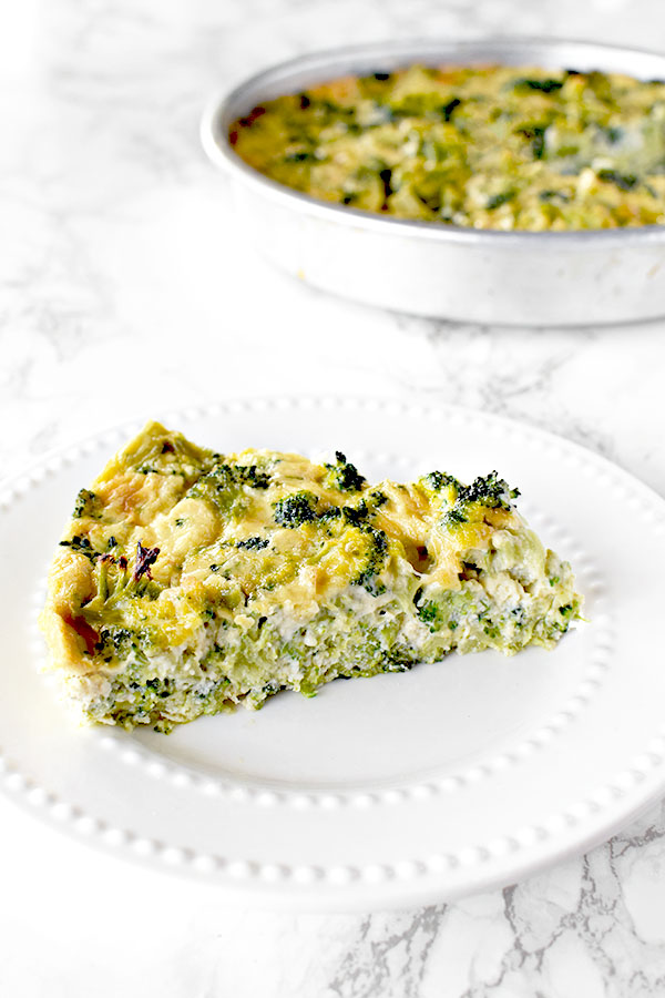 slice of broccoli kugel on a white plate with a pan of broccoli kugel in the background