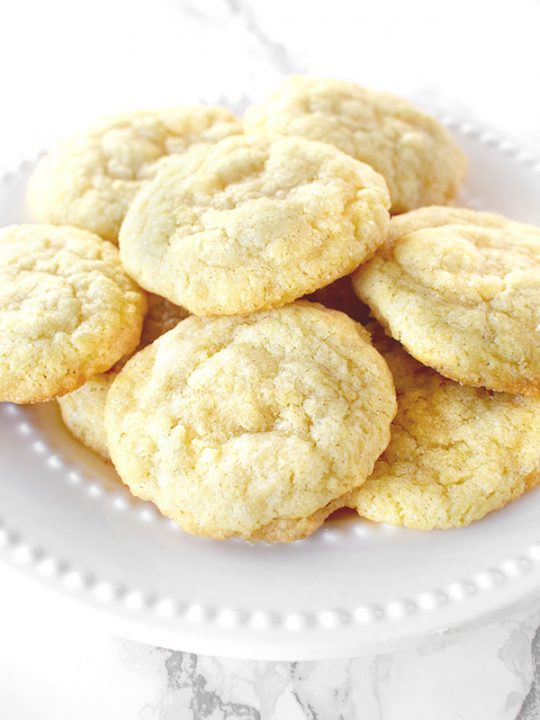 Dairy free sugar cookies piled up on a white plate on a white marble counter