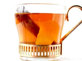 glass cup filled with mulled apple juice, a cinnamon stick, and an orange peel