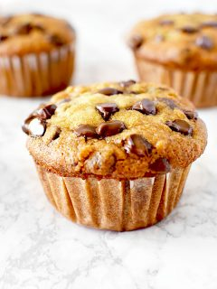 moist three banana chocolate chip muffins on a white marble counter