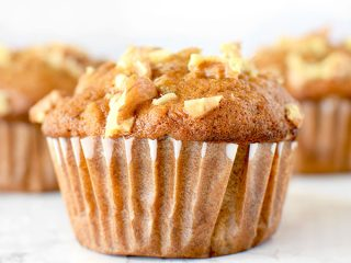 Three banana nut muffins on a white marble counter