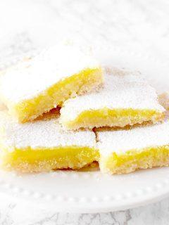four dairy free lemon bars piled on a plate