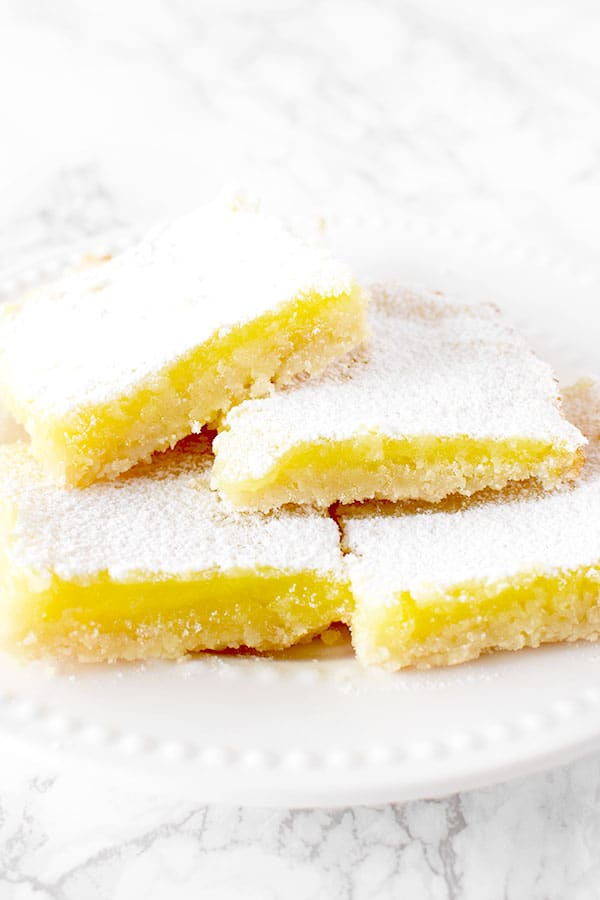 four dairy free lemon bars piled on a plate