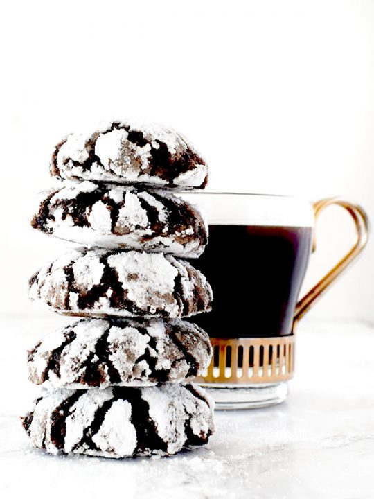 stack of mocha crinkle cookies near a cup of black coffee