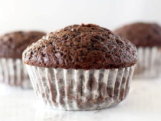 three chocolate muffins on a white counter