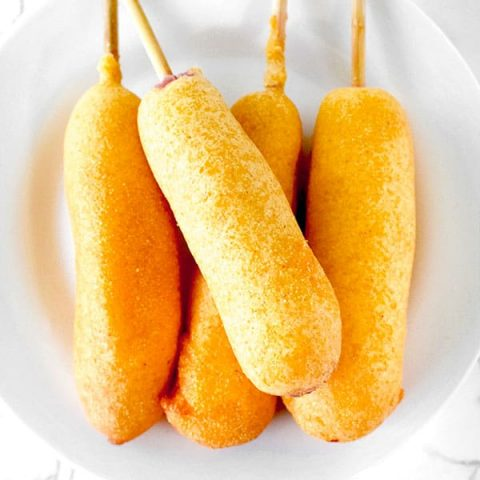 four corn dogs on a white plate