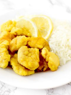 Chinese lemon chicken on a plate with rice