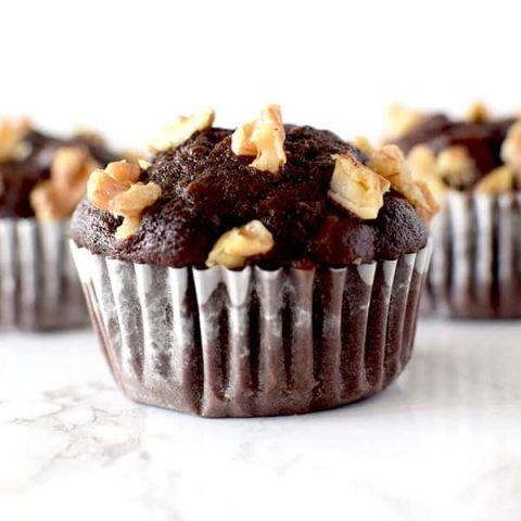three chocolate walnut muffins on a white marble counter
