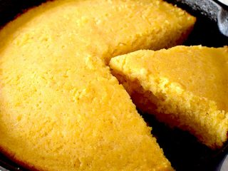 Cornbread in a cast iron skillet with a piece missing