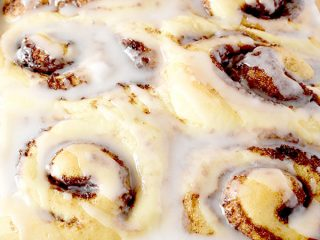 Six glazed no knead cinnamon rolls in a baking pan