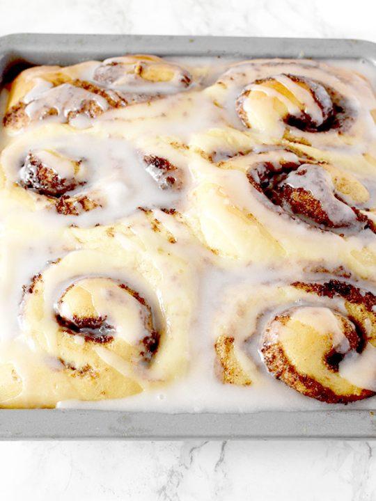 Six glazed no knead cinnamon rolls in a baking pan