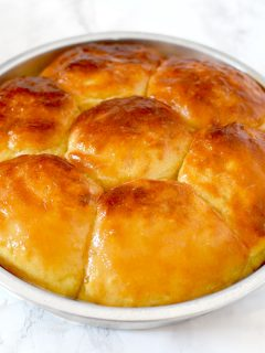 no knead yeast rolls in a round baking pan on a marble counter