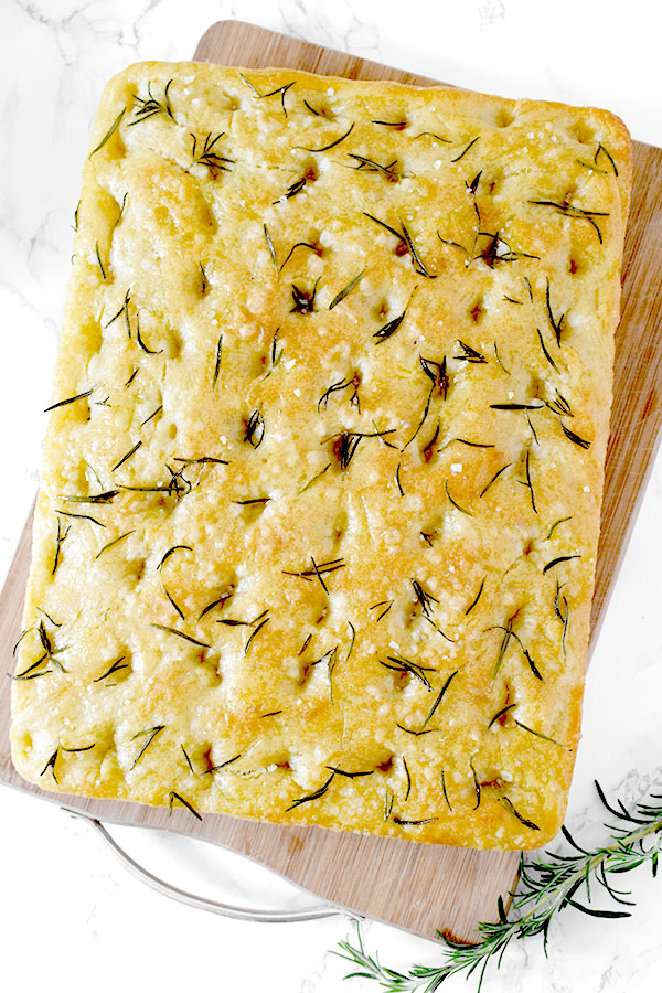 Rosemary and salt focaccia on a wooden cutting board