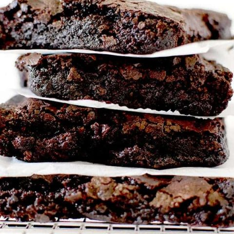 Fudge brownies stacked on a cooling rack