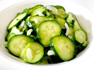 cucumber salad in a white bowl on a white marble counter