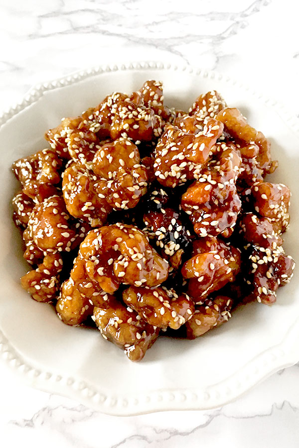 Chinese sesame chicken in a white bowl on a white marble counter