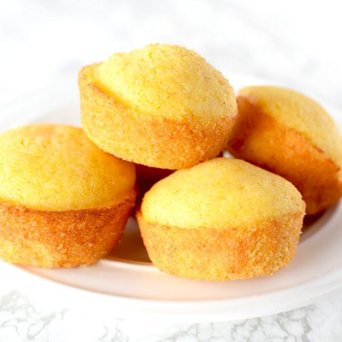 cornbread muffins piled on a plate on a white marble counter