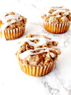 pumpkin muffins with streusel and icing on a white marble counter