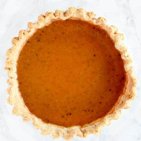birds eye view of butternut squash pie on a white marble counter