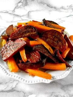 roasted beets and carrots on a white plate on a white marble counter
