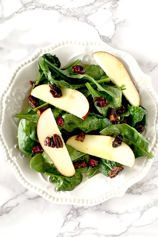 Apple cranberry salad featuring sliced apples on a bed of baby spinach topped with cranberries and nuts