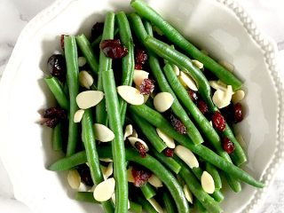 Green beans, cranberries, and dried almonds in a white bowl sitting on a white marble counter