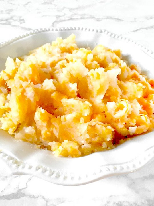 Mixed mashed potatoes in a white bowl on a white marble counter