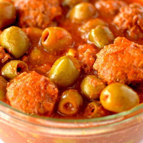 Glass bowl filled with meatballs and olives in tomato sauce