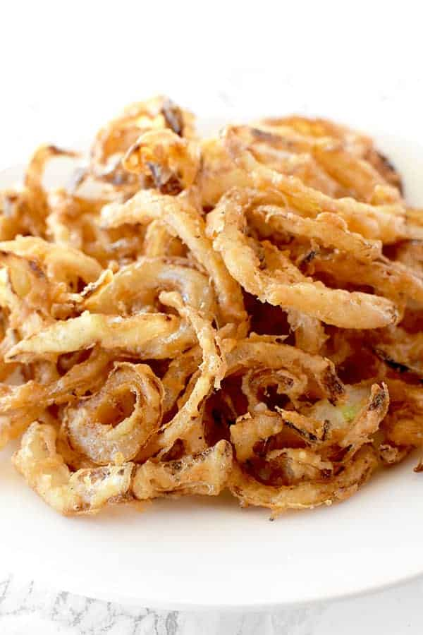 Homemade fried onions on a white plate on a white marble counter