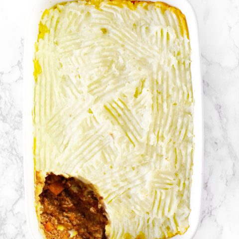 dairy free shepherd's pie or cottage pie in a white casserole dish on on a white marble counter